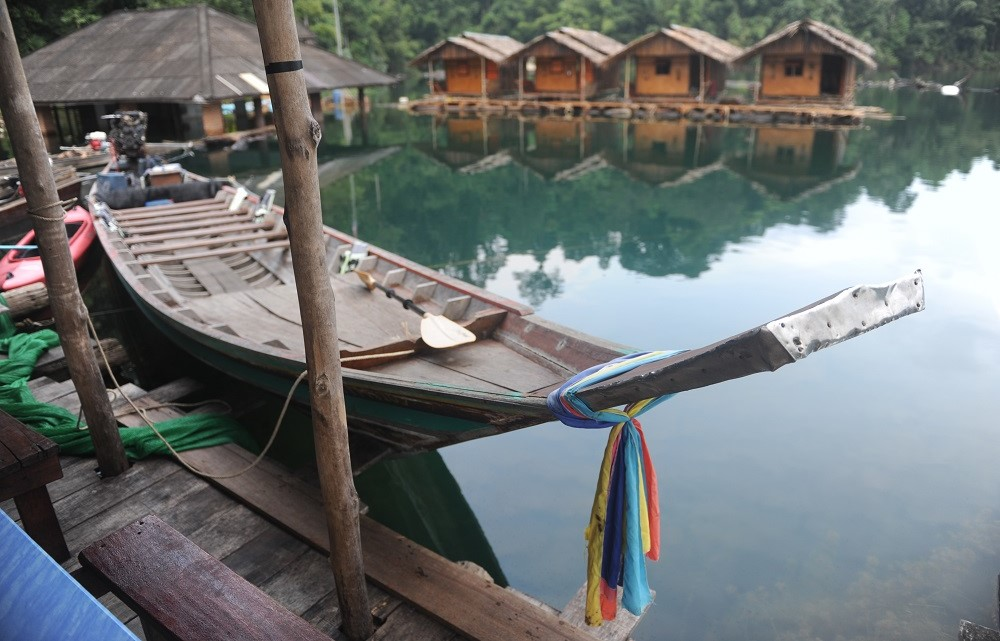 Long tail boat docked at National Parks raft houses on Cheow Lan lake.